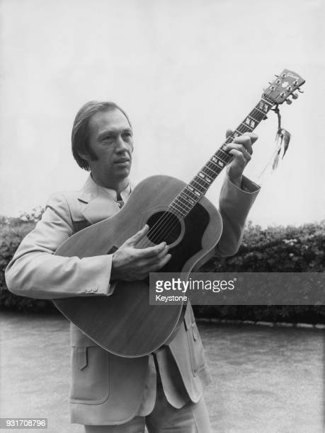 American actor David Carradine playing the guitar during the Cannes Film Festival France 20th May 1977 In 1976 he played folk singer Woody Guthrie in...