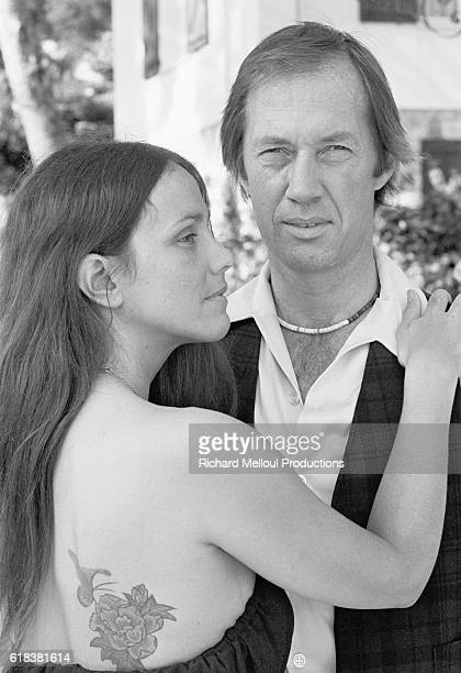 American actor David Carradine poses with his wife Linda who shows the tattoo on her back The couple were in Cannes to attend the 34th Cannes Film...