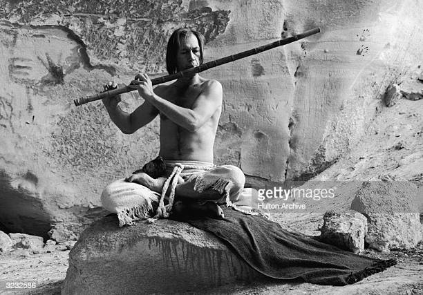 American actor David Carradine stars in the film 'Circle of Iron' He is sitting with his legs crossed on a blanket in a cave whilst playing a large...