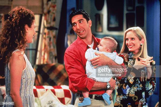 American actor David Schwimmer holds a baby as actors Jessica Hecht and Jane Sibbett look on in a still from the television series 'Friends' circa...