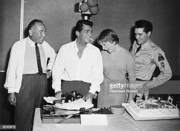American actor Dean Martin a cigarette dangling from his mouth celebrates his birthday with producer Hal Wallis actor Shirley MacLaine and singer and...