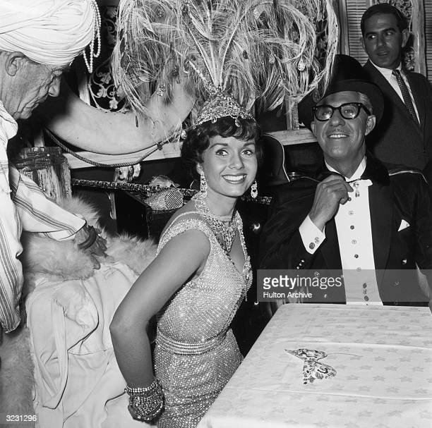 American actor Debbie Reynolds sits at a table with her second husband Harry Karl wearing costumes for The Thalians' Mardi Gras party Hollywood...