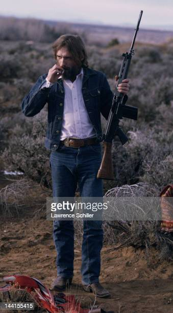 American actor Dennis Hopper holds a rifle and smokes during the filming of the documentary about him entitled 'The American Dreamer' Taos New Mexico...