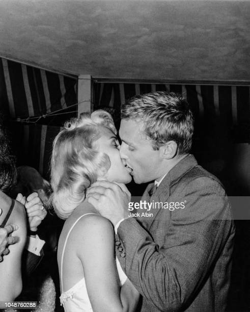 American actor Dennis Hopper kissing a young woman at a party given by Audra Martin in Los Angeles California 19th June 1957