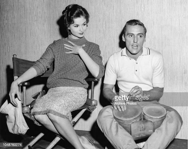 American actor Dennis Hopper playing a pair of bongo drums as American actress Susan Harrison looks on during the filming of 'Key Witness' directed...