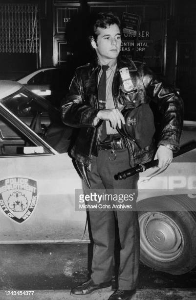 American actor Desi Arnaz Jr poses beside a New York Police Department car on the set of television movie 'To Kill a Cop' in New York City, New York,...