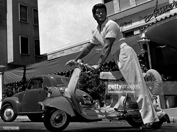 American actor Dewey Martin posing with a Vespa motorscooter by the Italian motorcycle manufacturer Piaggio Italy 1955