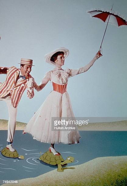 American actor Dick Van Dyke as Bert/Mr Dawes Sr and English actress Julie Andrews in the title role cross a river using turtles as steppingstones in...