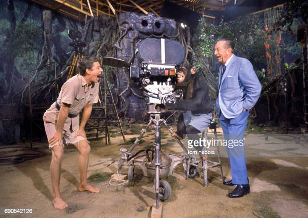 American actor Dick Van Dyke clowns around as chimpanzee actor Dinky looks through a film camera watched by producer Walt Disney on the set of the...
