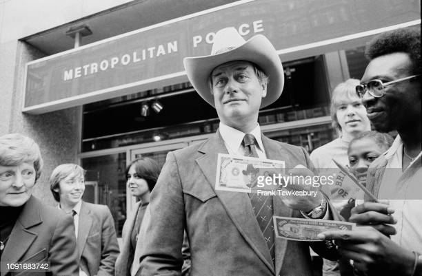 American actor director and producer Larry Hagman signing $100 bill from television show Dallas in which he plays 'JR Ewing' outside the Metropolitan...