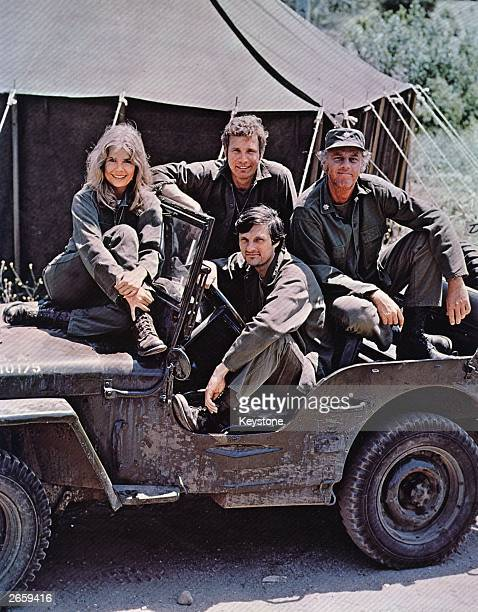 American actor, director and writer Alan Alda in the driving seat of a jeep, surrounded by Loretta Swit and other cast members of the hit television...