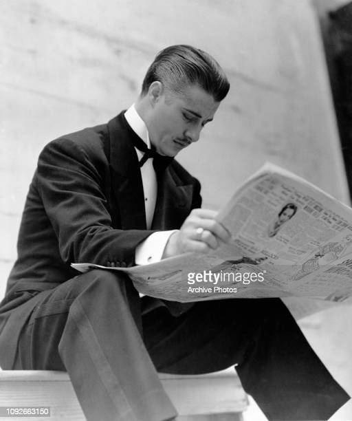 American actor Don Ameche reading the newspaper in formalwear May 1955