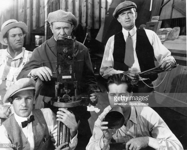 American actor Don Ameche speaks into a megaphone while sitting with a silent era film crew in a still from codirectors Irving Cummings and Malcolm...
