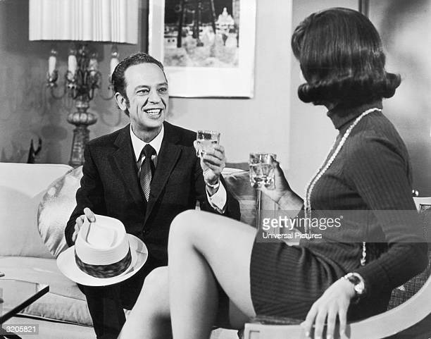 American actor Don Knotts smiles and raises his glass while toasting actor Yvonne Craig in a still from director Alan Rafkin's film 'How to Frame a...