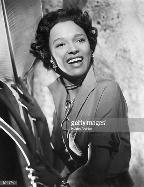 American actor Dorothy Dandridge smiles as she stands next to a large palm frond in a promotional portrait for director Robert Rossen's film 'Island...