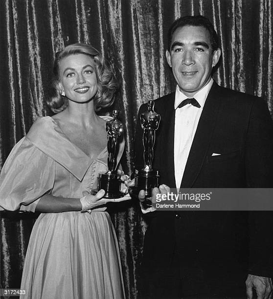 American actor Dorothy Malone and Mexicanborn actor Anthony Quinn hold their Best Supporting Actress and Supporting Actor Oscars Los Angeles...