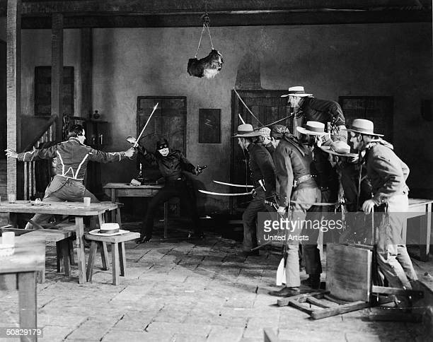 American actor Douglas Fairbanks fights off a group of men with swords drawn in a still from the film 'The Mark of Zorro' directed by Fred Niblo 1920