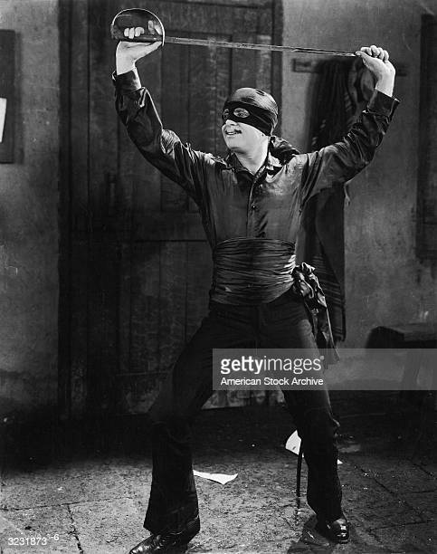 American actor Douglas Fairbanks holds a sword above his head as Zorro in a still from director Fred Niblo's film 'The Mark of Zorro'