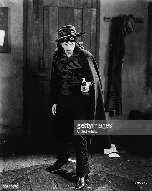 American actor Douglas Fairbanks poses in his masked costume aiming a gun in a still from the film 'The Mark Of Zorro' directed by Fred Niblo 1920