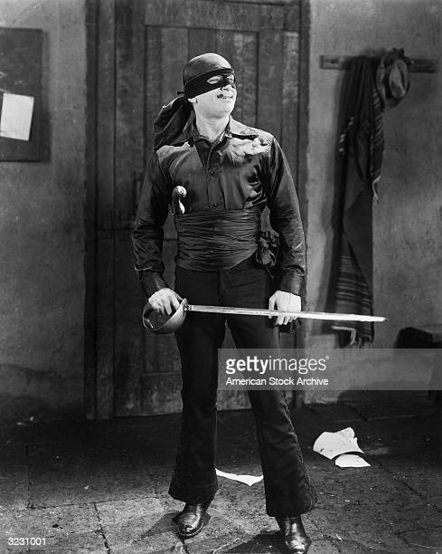 American actor Douglas Fairbanks Sr holds a sword in a still from director Fred Niblo's film, 'The Mark of Zorro'. He wears a mask, a sash, and...
