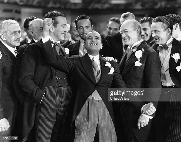 American actor Douglas Fairbanks Sr. Reacts with joy amidst a crowd of formally dressed men in a still from director Edmund Goulding's film 'Reaching...