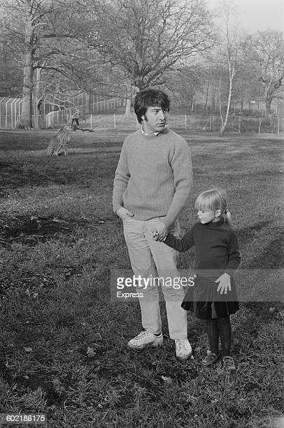 American actor Dustin Hoffman and his adopted daughter Karina being watched by a cheetah at Windsor Safari Park, UK, 10th January 1971.