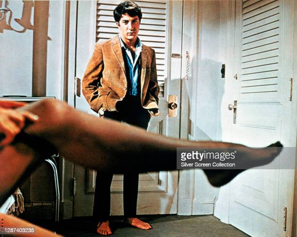 American actor Dustin Hoffman as Benjamin Braddock, watching his older lover Mrs Robinson get dressed in a promotional still from the film 'The...