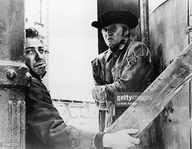 American actor Dustin Hoffman smokes a cigarette and holds up a slat of wood as American actor Jon Voight shivers from the cold in a still from the...