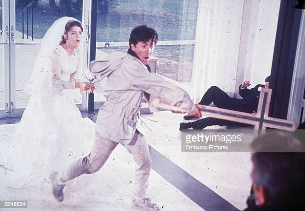 American actor Dustin Hoffman uses a cross as a weapon to keep people away while he attempts to flee a church with American actor Katharine Ross, in...