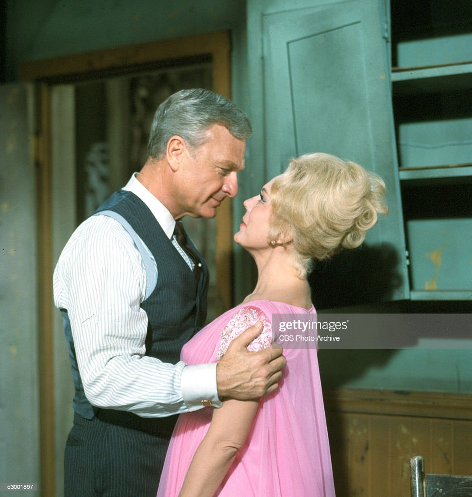 American actor Eddie Albert (1906 - 2005) and Hungarian-born actress Eva Gabor (1919 - 1995) share an intimate moment in a scene from the television situation comedy 'Green Acres,' June 1967.