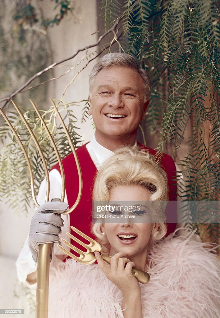 American actor Eddie Albert (1906 - 2005) holds a gold colored pitchfork and stands behind his tv wife Hungarian-born actress Eva Gabor (1919 - 1995), who holds a gold colored hand rake, as they pose for a publicity portrait for the CBS rural fish out of water sitcom 'Green Acres,' late 1960s.