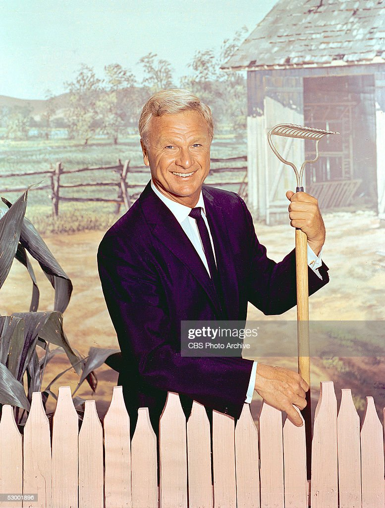 American actor Eddie Albert (1906 - 2005) stands behind a fence against a backdrop of a farm and holds a rake in a promotional portrait for the TV series 'Green Acres,' June 1965.