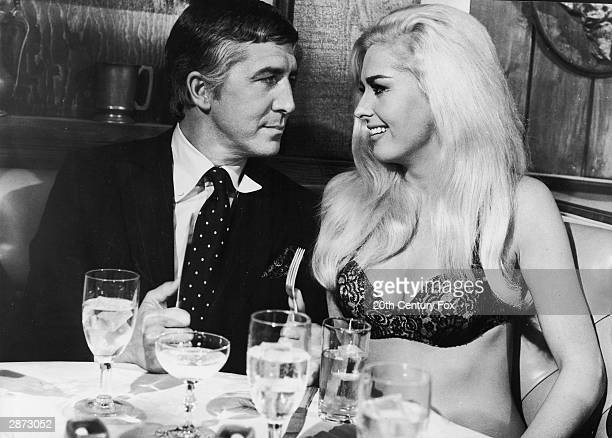 American actor Edy Williams speaks to an unidentified man at a restaurant table wearing only a bra in a still from the film 'The Secret Life of An...