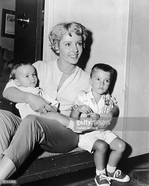 American actor Elizabeth Taylor wearing aging makeup sitting with her two sons Christopher and Michael Wilding Jr on the porch of her dressing room...