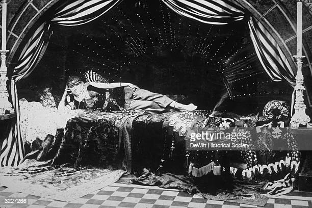 American actor Elsie Baker wearing a harem girl costume as she reclines on a lavish Middle Eastern tent bed in an unidentified film still