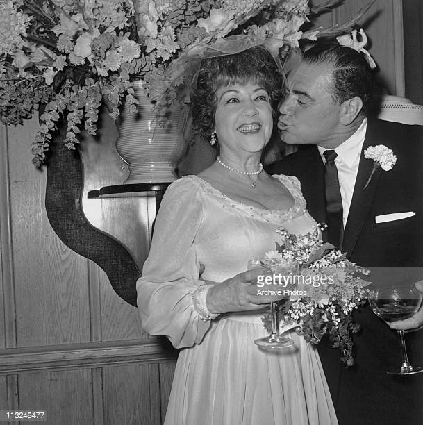 American actor Ernest Borgnine leans in to kiss actress Ethel Merman during their wedding reception in Beverly Hills California in June 1964 The...