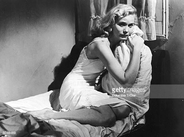 American actor Eva Marie Saint sits on a bed and clutches a pillow in a still from the film, 'On The Waterfront,' directed by Elia Kazan.