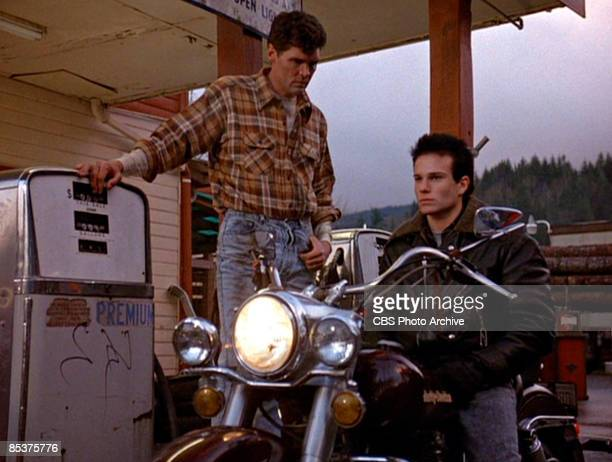 American actor Everett McGill stands beside a fuel pump in a gas station as actor James Marshall sits astribe a motorcycle in a scene from the pilot...
