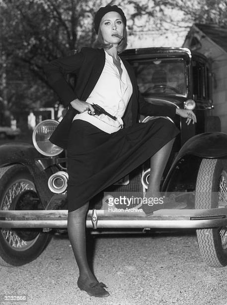American actor Faye Dunaway as bank robber Bonnie Parker in a still from director Arthur Penn's film 'Bonnie and Clyde' She is posing with her foot...