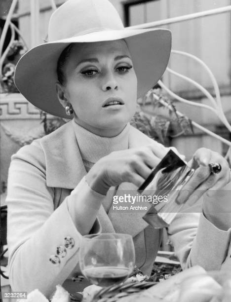 American actor Faye Dunaway pulls a cigarette out of a silver case in a still from director Norman Jewison's film 'The Thomas Crowne Affair' Dunaway...