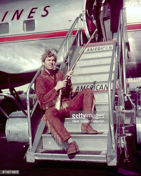 American actor Fess Parker dressed as reallife frontiersman Davy Crockett who he plays in the television miniseries 'Davy Crockett' whilst sitting on...