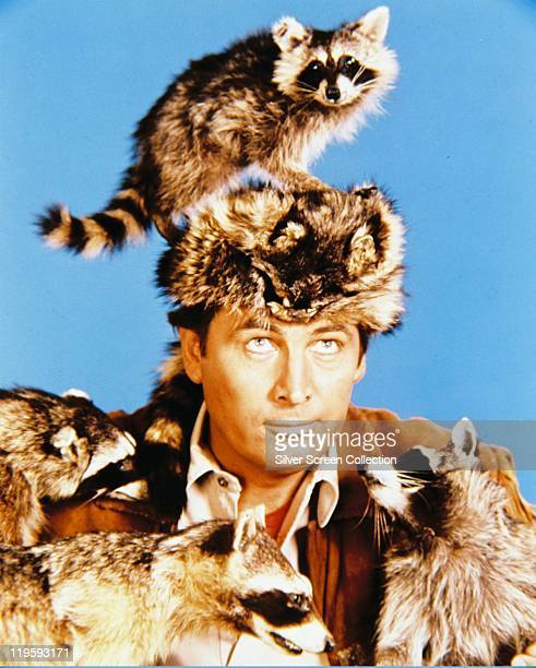 Fess Parker US actor wearing a coonskin hat as he poses with a number of racoons in a publicity portrait for the television series 'Davy Crockett...