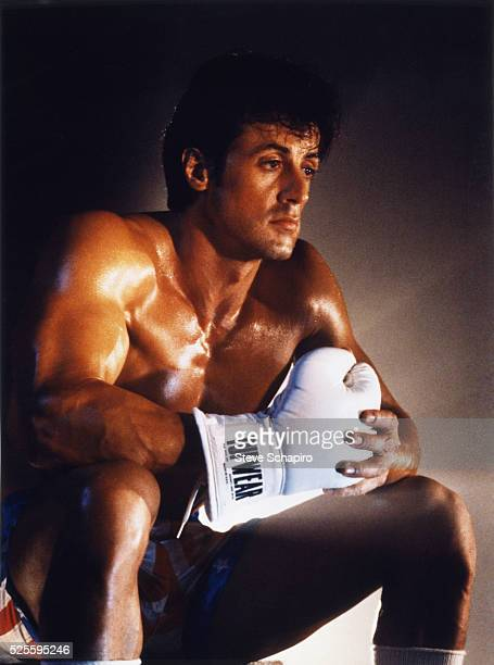 American actor, film director and screenwriter Sylvester Stallone in character as Rocky Balboa, holding Apollo Creed's glove, in a scene from the...
