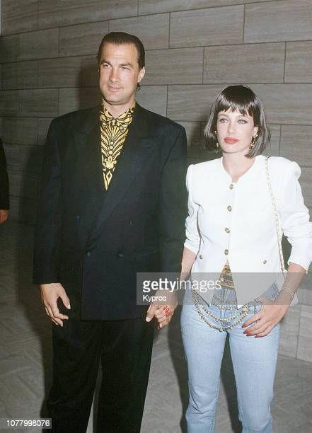 American actor film producer screenwriter martial artist and musician Steven Seagal with his wife Americanborn English actress and model Kelly...