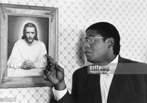 American actor Forest Whitaker points to a painting of Jesus in a publicity still from the film 'A Rage in Harlem' 1991