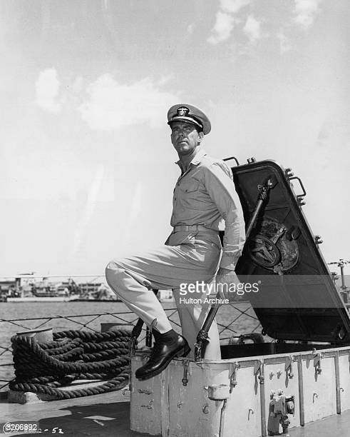 American actor Fred MacMurray , wearing a naval uniform, exits a hatch onto a ship's deck in a still from director Edward Dmytryk's film, 'The Caine...