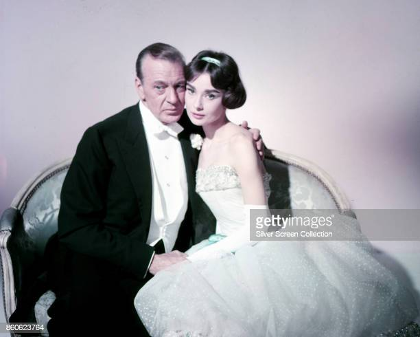 American actor Gary Cooper and British actress Audrey Hepburn both in formal wear sit on a loveseat in a scene from 'Love in the Afternoon' France...