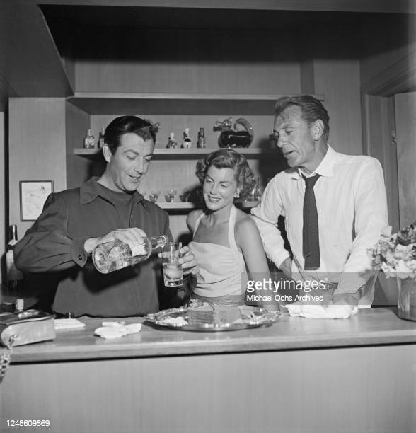 American actor Gary Cooper and his wife, actress Veronica or 'Rocky', play host to actor Robert Taylor at their home in Aspen, Colorado, circa 1952.