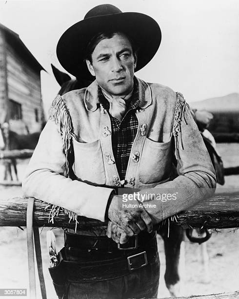 American actor Gary Cooper , dressed in a fringed jacket and cowboy hat with a gun belt and holster around his waist, in a publicity still for the...