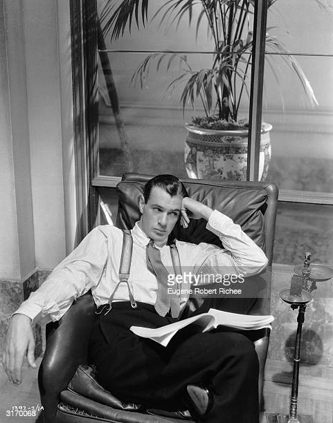 American actor Gary Cooper lounging in a leather armchair.